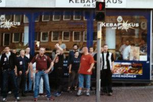 Kassel 2002: Stephan Ernst (rechts) links neben ihm im roten T-Shirt Markus Eckel, direkt hinter Eckel ist Stephan Pfingsten (hellblaues Hemd) und hinter ihm links vor der Scheibe ist Martin Gotthardt (blauer Pulli) – Bildrechte: NSU Watch